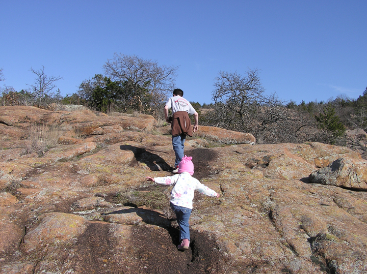 Two children hike up a brown rock outcropping in the Wichita Mountains Wilderness.